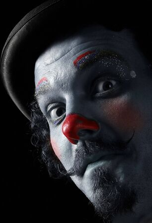 a portrait of a funny clown on black photo