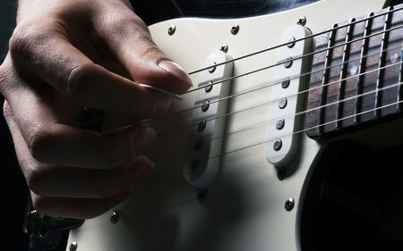 man is playing electric guitar on blue