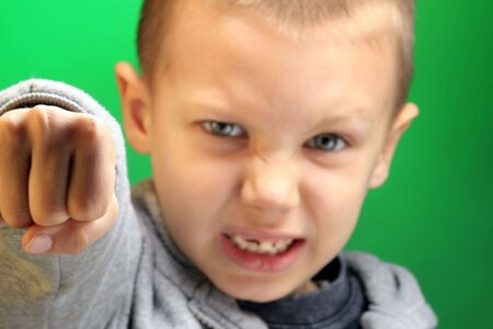 photo of a boy with ugly grimase on green photo
