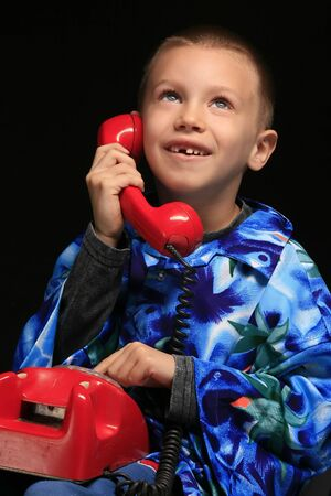 a boy is talking on the red phone photo