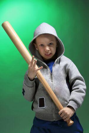 hooligan boy with baseball stick on green  Stock Photo