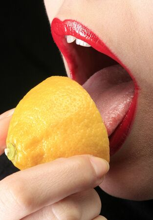 part of a woman face with tongue which is licking lemon photo