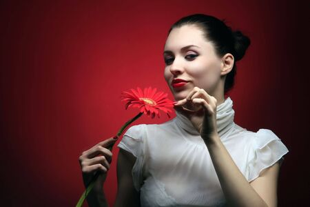 girl is smiling and holding red flower photo