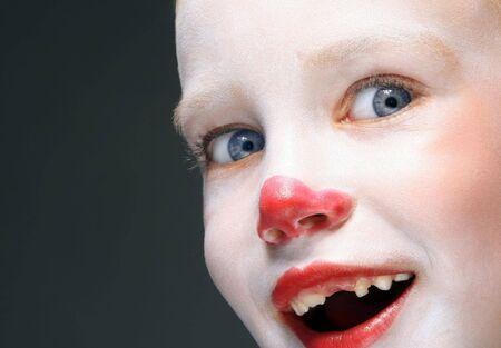laugher: portrait of make up clown boy with red nose Stock Photo