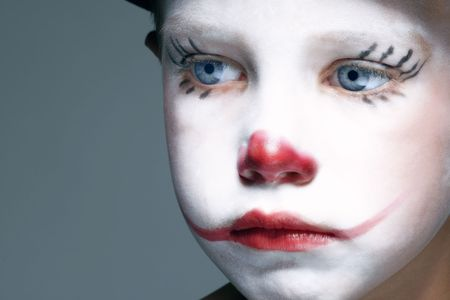 portrait of make up clown boy with red nose photo