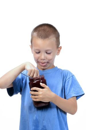 marmelade: kid eating marmelade , while smearing his face with marmelade Stock Photo