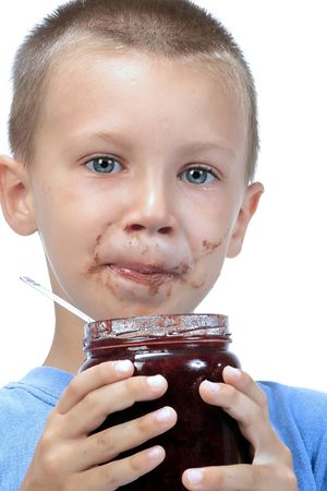 kid eating marmelade , while smearing his face with marmelade photo