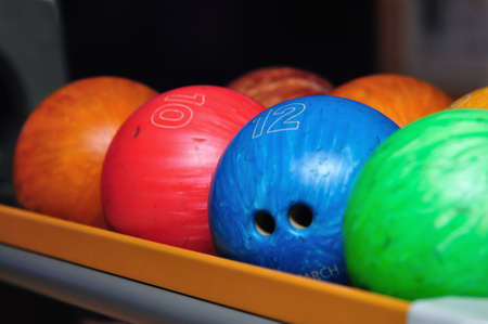 A variety of colorful bowling balls sitting in the ball return at the bowling alley. Stock Photo - 4982381