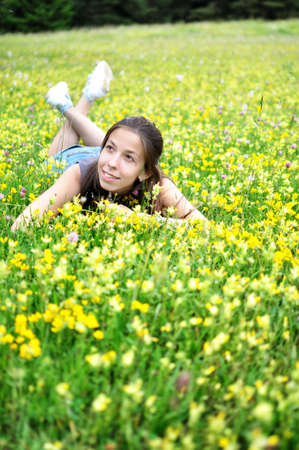 Smiling girl resting on the green grass and flowers.