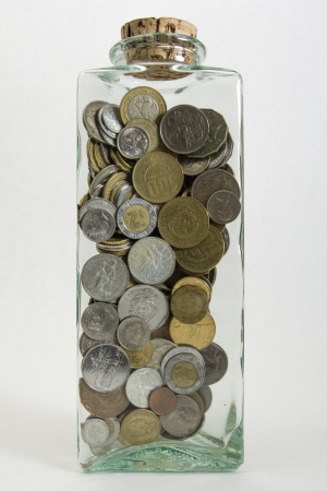 canadian coin: A glass jar filled with coins from a variety of countries isolated on a white background    Stock Photo