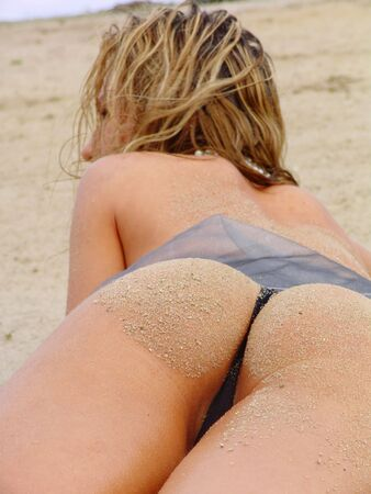 Seductive denuded girl in bikini to rest upon beach photo
