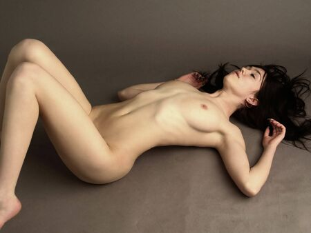 Denuded sexual girl, brunette rests upon floor