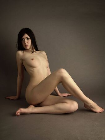 Denuded sexual girl, brunette sits on floor
