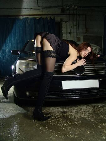 Beautiful sexy girl on background expensive black car