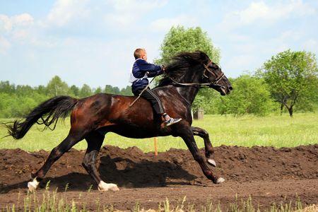 The young horseman boy on horseback. Traditional horse racing in Bashkortostan on holiday sabantuy photo