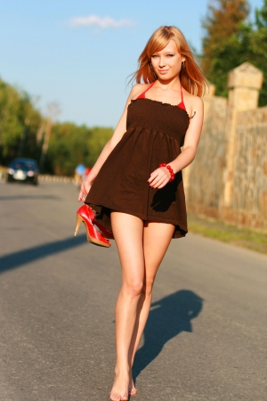 1 adult only: Young beautiful girl in short dress on road Stock Photo
