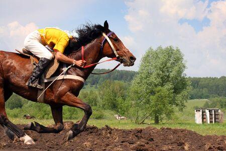 The young horseman on horseback. Traditional horse racing in Bashkortostan on holiday sabantuy photo