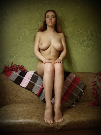 Beautiful sexual denuded girl on sofa on background green wall