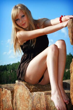 Young beautiful girl in short dress on background blue sky Stock Photo