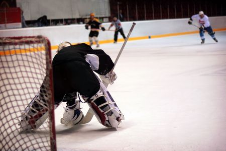 Hockey goalie in generic black equipment protects gates