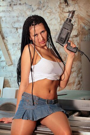 Seductive girl is with african hairstyle to keep in hand drill photo