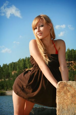one teenage girl only: Young beautiful girl in short dress on background blue sky Stock Photo
