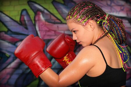 muay: Portrait of a girl with red boxing gloves over graffiti background
