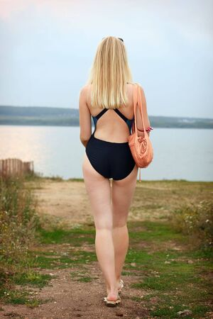 Lovely young girl in athletic swimsuit on beach photo