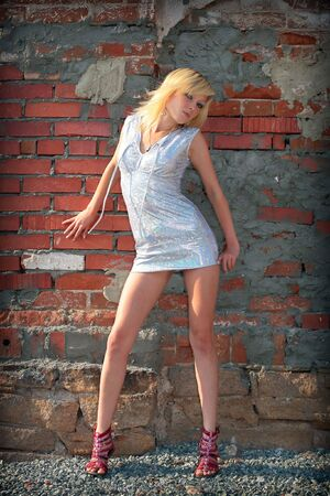 Beautiful blond sexy girl beside brick wall photo