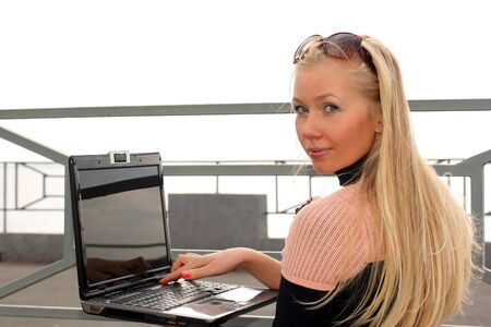 Young girl working with laptop on outdoors photo