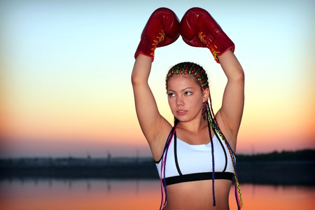 Portrait of a girl with red boxing gloves on background of the sundown