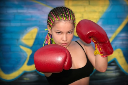Portrait of a girl with red boxing gloves over graffiti background photo