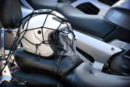 helmet seat: White helmet on leather seat of the motorcycle Stock Photo