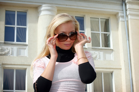 Beautiful blonde girl in sunglasses in the city