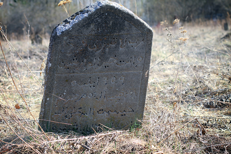 Tombstone with Arabic inscriptions. The ancient Muslim cemetery abandoned, found in the woods. Bashkortostan, Russia Stock Photo