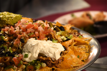 A photo of gourmet nachos, with tomatoes, guacamole, sour cream, olives and cheese with blurred appetizer in the background.