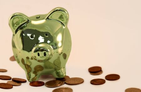 Green piggy bank with change scattered around