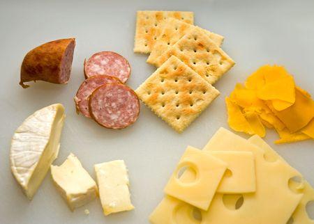 ブリー、チェダー チーズ、スイス チーズ クラッカーと農夫のソーセージ