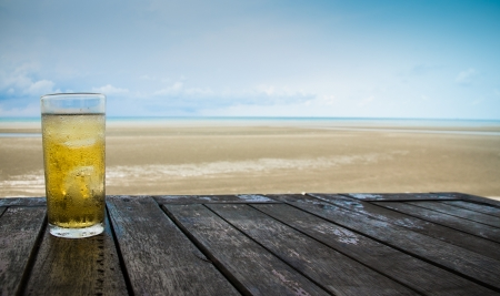 beach drink: Cold beer on wood table in front the sea of Thailand