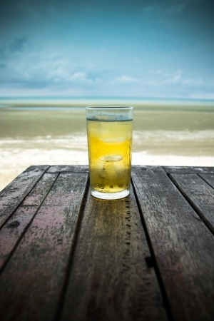 Cold beer on wood table in front the sea of Thailand