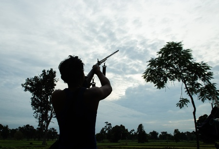 Man shoot gun on sky photo
