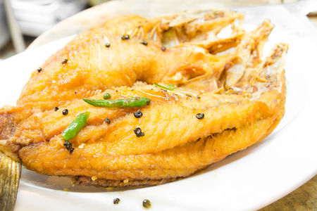 Fried snapper with chili sauce on dish photo