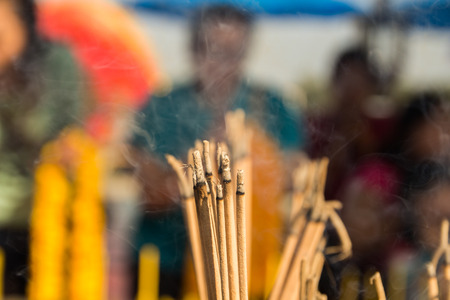 Yellow incense sticks burning in an altar at a Taoist temple photo