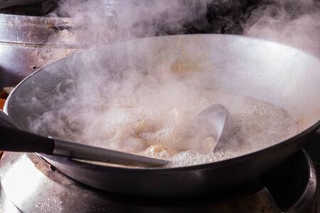 Boiling water inside a kitchen iron pot photo