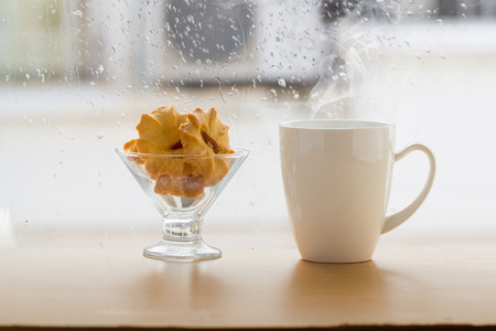 Cookies in glass with hot drink on table beside window,relax time