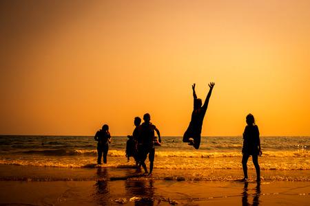 日没の跳躍の友人のシルエット 写真素材