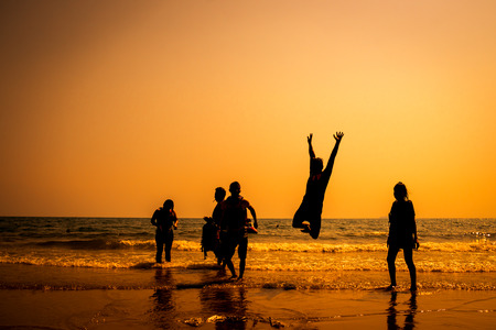 Silhouette of friends jumping in sunset Stock fotó