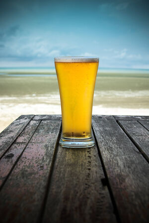 single beer: Cold beer on wood table in front the sea of Thailand