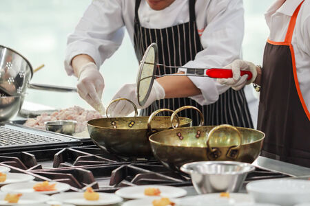 cooking utensils: Busy cooking of chefs in restaurant kitchen