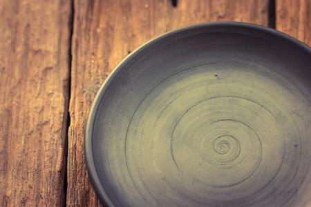 grunge flatware: Dark plate  on old wooden table